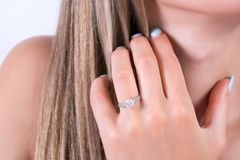 Νέο θηλυκό χέρι με το γαμήλιο δαχτυλίδι δέσμευσης στην εκμετάλλευση δάχτυλων και χεριών στην τρίχα στοκ εικόνα με δικαίωμα ελεύθερης χρήσης