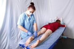 Νέο θηλυκό beautician γιατρών που κάνει δίπλα στο τακούνι του αριστερού ποδιού μιας νέας γυναίκας σε ένα κόκκινο φόρεμα στοκ εικόνες με δικαίωμα ελεύθερης χρήσης