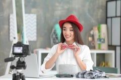 Νέο θηλυκό blogger με το βίντεο καταγραφής δεσμών καπέλων και τόξων Στοκ Εικόνες