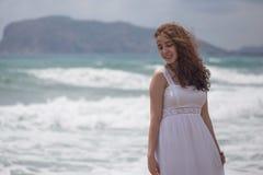 Νέο θηλυκό brunette με την κυματιστή τρίχα που φορά το άσπρο φόρεμα Στοκ Φωτογραφία