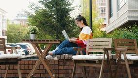 Νέο θηλυκό freelancer με το lap-top στον υπαίθριο καφέ απόθεμα βίντεο
