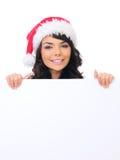 Νέο θηλυκό καπέλο Santa εφήβων πίσω από το λευκό πίνακα Στοκ Εικόνες