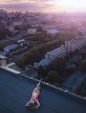 Νέο θηλυκό που βρίσκεται και που κάνει ηλιοθεραπεία στη στέγη και το υπόβαθρο της άποψης πόλεων Ημέρα, έξω στοκ εικόνες