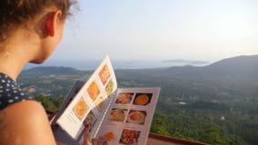 Νέο θηλυκό που εξετάζει τις επιλογές στο εστιατόριο φιλμ μικρού μήκους