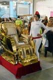 Νέο θηλυκό πρότυπο δίπλα σε μια χρυσή καρέκλα για την ομορφιά Intercharm ΧΙΙ διεθνής αρωματοποιία και έκθεση Μόσχα καλλυντικών Στοκ Φωτογραφίες