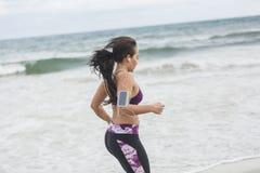 Νέο θηλυκό δρομέων στην παραλία Όμορφο κατάλληλο μικτό RA Στοκ Φωτογραφίες