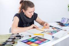 Νέο θηλυκό σκίτσο σχεδίων καλλιτεχνών που χρησιμοποιεί sketchbook με το μολύβι στον εργασιακό χώρο της στο στούντιο Πορτρέτο πλάγ Στοκ Φωτογραφία