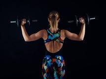 Νέο θηλυκό bodybuilder με το τέλειο ισχυρό μυϊκό σώμα που φορά sportswear τη φόρμα γυμναστικής που ασκεί με τα βάρη Οπισθοσκόπος Στοκ φωτογραφία με δικαίωμα ελεύθερης χρήσης