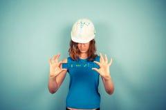 Νέο θηλυκό buidler που κρατά ένα επίπεδο Στοκ Εικόνα