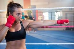 Νέο θηλυκό punching μπόξερ ενάντια στο εγκιβωτίζοντας δαχτυλίδι Στοκ Εικόνα