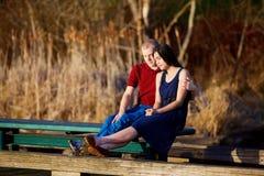 Νέο διαφυλετικό ζεύγος που απολαμβάνει το χρόνο μαζί στην ξύλινη αποβάθρα ο στοκ φωτογραφία