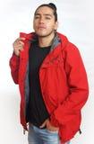 Νέο ισπανικό άτομο με τη μαζευμένη τρίχα που γίνεται στο κουλούρι που φορά τη μαύρη μπλούζα και το κόκκινο σακάκι, με ένα χέρι στ Στοκ εικόνα με δικαίωμα ελεύθερης χρήσης