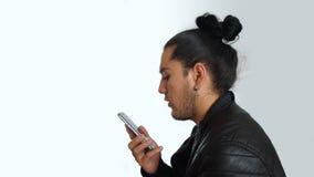 Νέο ισπανικό άτομο με τη μαζευμένη τρίχα που γίνεται στο μαύρο φόρεμα και το μαύρο σακάκι δέρματος, που μιλούν μέσω του κινητού τ Στοκ Φωτογραφία