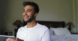 Νέο ισπανικό άτομο που χρησιμοποιεί τον ευτυχή τύπο χαμόγελου υπολογιστών ταμπλετών που κουβεντιάζει on-line πέρα από το μεγάλο π απόθεμα βίντεο