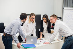 Νέο κάθισμα επιχειρηματιών στην αρχή κατά τη διάρκεια της συνεδρίασης και συζήτηση με τη γραφική εργασία που χρησιμοποιεί τα lap- Στοκ Εικόνα
