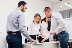 Νέο κάθισμα επιχειρηματιών στην αρχή κατά τη διάρκεια της συνεδρίασης και συζήτηση με τη γραφική εργασία που χρησιμοποιεί τα lap- Στοκ Φωτογραφίες