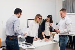 Νέο κάθισμα επιχειρηματιών στην αρχή κατά τη διάρκεια της συνεδρίασης και συζήτηση με τη γραφική εργασία που χρησιμοποιεί τα lap- Στοκ εικόνες με δικαίωμα ελεύθερης χρήσης