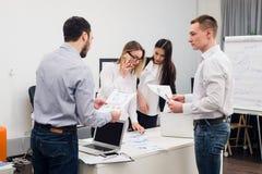 Νέο κάθισμα επιχειρηματιών στην αρχή κατά τη διάρκεια της συνεδρίασης και συζήτηση με τη γραφική εργασία που χρησιμοποιεί τα lap- Στοκ εικόνα με δικαίωμα ελεύθερης χρήσης