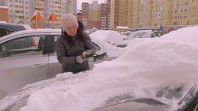 Νέο καθαρίζοντας χιόνι οδηγών γυναικών από το αυτοκίνητο στο χώρο στάθμευσης στη συγκυριαρχία απόθεμα βίντεο