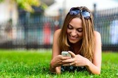 Νέο καθιερώνον τη μόδα κορίτσι (21) που κοιτάζει βιαστικά το Διαδίκτυο με το τηλέφωνο κυττάρων της Στοκ εικόνα με δικαίωμα ελεύθερης χρήσης