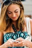 Νέο καθιερώνον τη μόδα κορίτσι (21) που κοιτάζει βιαστικά το Διαδίκτυο με το τηλέφωνο κυττάρων της Στοκ εικόνες με δικαίωμα ελεύθερης χρήσης