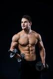 Νέο και κατάλληλο αρσενικό πρότυπο που θέτει τους μυς του που αντλούν επάνω με τους αλτήρες σε μια γυμναστική που κοιτάζει στο αρ στοκ εικόνες με δικαίωμα ελεύθερης χρήσης