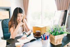 Νέο και όμορφο ασιατικό μικρό γραφείο εργασίας ιδιοκτητών επιχείρησης στο σπίτι, που οργανώνει την εντολή αγοράς Παράδοση συσκευα στοκ φωτογραφία