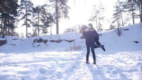 Νέο και όμορφο ερωτευμένο περπάτημα ζευγών στα χειμερινά ξύλα φιλμ μικρού μήκους