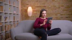 Νέο και όμορφο θηλυκό brunette freelancer που εργάζεται με την ταμπλέτα που συγκεντρώνεται στο σπίτι απόθεμα βίντεο