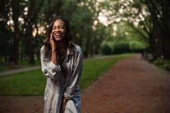 Νέο και όμορφο μαύρο κορίτσι που μιλά στο τηλέφωνο και το γέλιο Κορίτσι που φορά τα περιστασιακά ενδύματα και μια ΚΑΠ Στοκ φωτογραφίες με δικαίωμα ελεύθερης χρήσης