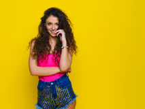 Νέο και όμορφο σγουρό κορίτσι σε ένα ρόδινο πουκάμισο και μπλε σορτς ο Στοκ Εικόνες