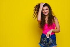 Νέο και όμορφο σγουρό κορίτσι σε ένα ρόδινο πουκάμισο και μπλε σορτς ο Στοκ Εικόνα