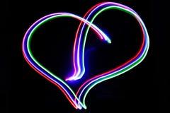 Νέο καρδιών αστραπής που παράγεται με τα χρωματισμένα φω'τα και ένα αργό SH Στοκ Εικόνα