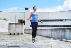 Νέο, κατάλληλο και φίλαθλο κορίτσι που πηδά με ένα πηδώντας σχοινί Στοκ εικόνα με δικαίωμα ελεύθερης χρήσης