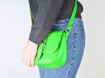 Νέο κατάλληλο κορίτσι στα τζιν και πουλόβερ που κρατά μια τσάντα δέρματος στοκ φωτογραφίες