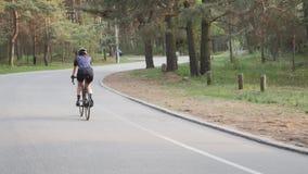 Νέο κατάλληλο οδηγώντας ποδήλατο κοριτσιών στο πάρκο που φορά το μαύρο κράνος, το μπλε Τζέρσεϋ και τα γυαλιά φιλμ μικρού μήκους