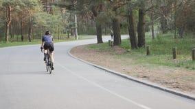 Νέο κατάλληλο οδηγώντας ποδήλατο κοριτσιών στο πάρκο που φορά το μαύρο κράνος, το μπλε Τζέρσεϋ και τα γυαλιά o απόθεμα βίντεο