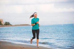 Νέο κατάλληλο τέντωμα κοριτσιών στην παραλία στην ανατολή στοκ εικόνα με δικαίωμα ελεύθερης χρήσης