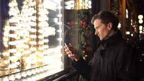 Νέο καυκάσιο άτομο που μιλά στο κινητό τηλέφωνο σε μια πολυάσχολη αστική οδό το βράδυ φιλμ μικρού μήκους
