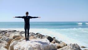 Νέο καυκάσιο άτομο που στέκεται σε μια δύσκολη παραλία με τις αγκάλες ανοικτές ευρέως ενώ ισχυρά κύματα που χτυπούν το ράντισμα α φιλμ μικρού μήκους