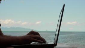 Νέο καυκάσιο άτομο που χρησιμοποιεί το lap-top με την άποψη θάλασσας Μακρινή εργασία και ανεξάρτητη έννοια τα αρσενικά χέρια κλεί απόθεμα βίντεο