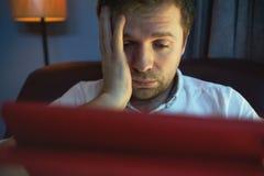 Νέο καυκάσιο άτομο στο φορητό προσωπικό υπολογιστή με την ελαφριά αντανάκλαση από την οθόνη στο πρόσωπο που λειτουργεί στο σπίτι Στοκ Φωτογραφίες