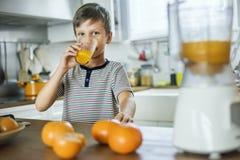 Νέο καυκάσιο αγόρι που πίνει το χυμό από πορτοκάλι Στοκ Φωτογραφία