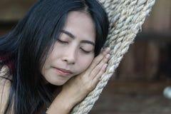 Νέο καυκάσιο ασιατικό κορίτσι που ταλαντεύεται σε μια αιώρα σε μια ευχάριστη τεμπελιά ενός βραδιού Σαββατοκύριακου στοκ φωτογραφία με δικαίωμα ελεύθερης χρήσης