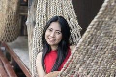 Νέο καυκάσιο ασιατικό κορίτσι που ταλαντεύεται σε μια αιώρα σε μια ευχάριστη τεμπελιά ενός βραδιού Σαββατοκύριακου στοκ φωτογραφίες