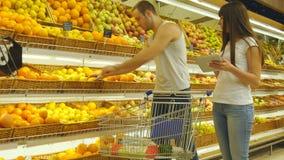 Νέο καυκάσιο ζεύγος που περπατά σε μια υπεραγορά με ένα καροτσάκι αγοράς και που επιλέγει τα φρέσκα μήλα Το άτομο βάζει τα φρούτα απόθεμα βίντεο