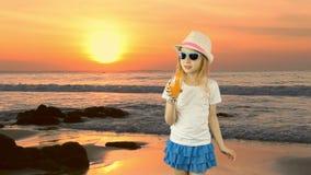 Νέο καυκάσιο κορίτσι που στέκεται και που πίνει το κοκτέιλ χυμού από πορτοκάλι μέσω του αχύρου Ορίζοντας παραλιών ηλιοβασιλέματος απόθεμα βίντεο