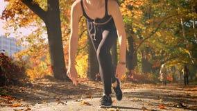 Νέο καυκάσιο κορίτσι στο jumpsuit στην αρχική γραμμή που παίρνει έτοιμη να τρέξει στο φθινοπωρινό πάρκο απόθεμα βίντεο