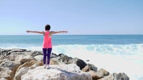 Νέο καυκάσιο κορίτσι brunette που στέκεται σε μια δύσκολη παραλία με τις αγκάλες ανοικτές ευρέως ενώ ισχυρά κύματα που χτυπούν το απόθεμα βίντεο