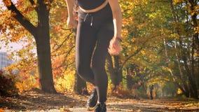 Νέο καυκάσιο λεπτό κορίτσι που προετοιμάζεται να τρέξει στην αρχική γραμμή στο φθινοπωρινό υπόβαθρο φιλμ μικρού μήκους